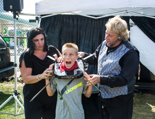 East Northport, NY - Mark and Kym Schussmann from The Magic of Mark and Kym Magic Show perform a sword illusion on an audience member at the East Northport Festival on September 6th, 2014.